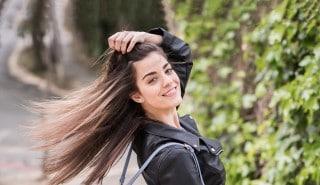Modelo con una chaqueta negra meciendo su largo cabello lacio sobre sus hombros.
