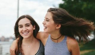 Dos modelos con cabello suave, abrazadas y sonriendo.