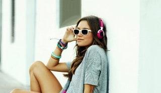 Mujer con cabello largo y lacio, sentada sobre un skate y escuchando música con auriculares para ilustrar la página de la línea Sedal Caspa Control.