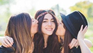 Tres amigas felices de cabello largo, divirtiéndose juntas.