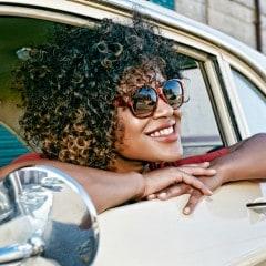 Mujer con cabello enrulado sonriendo, con anteojos de sol, asomanda por la ventanilla del auto.