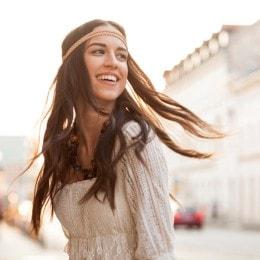 Mujer con cabello castaño graso, con una blusa beige, mirando por encima de su hombro y sonriendo en la calle.